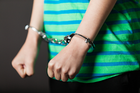 Photo pour Close up on pair of hands from child or teenager in green and blue shirt tied with metal handcuffs - image libre de droit