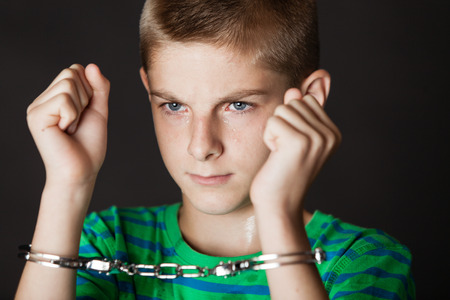 Foto de Single teenaged boy with both arms up near face while chained in handcuffs while grinning - Imagen libre de derechos