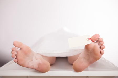Photo for Boys body or cadaver lying on a mortuary slab covered with a white sheet with a blank tag tied to his toe awaiting identification, view from the bare feet - Royalty Free Image