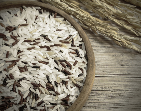 Close up white and red rice mixed on the wooden plate and rice plant ,  uncooked raw cereals ( Vintage tone color )