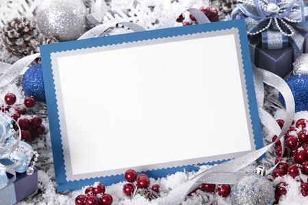 Foto de Blank Christmas card or invitation with blue envelope surrounded by decorations. Space for copy. - Imagen libre de derechos