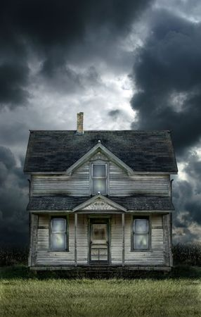 Old haunted farmhouse under a stormy sky.