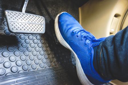 Foto de The gas pedal brake pedal on the blue shoes. - Imagen libre de derechos