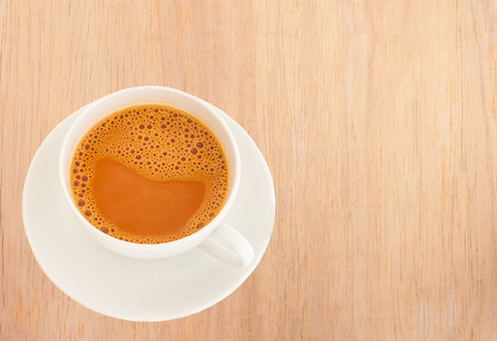 Photo for Hot milk tea in a white cup on wooden background - Royalty Free Image