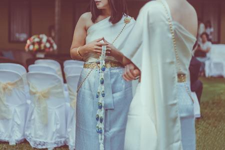 Foto de Happiness Bridesmaids in Thai dresses waiting for important time in Thai wedding ceremony - Imagen libre de derechos
