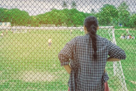 Photo pour Back view of female parent cheering children playing football in school. - image libre de droit