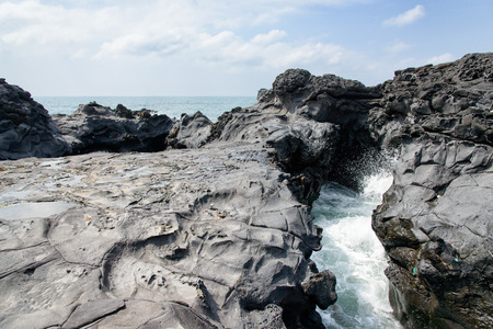 Photo pour landscape with Spray of water by struck Seawater through tunnel between rocks at the coast near the Olle trail route 16  in Jeju Island, Korea. - image libre de droit