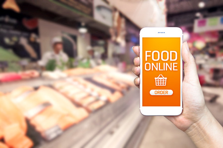 Foto de Hand holding mobile with grocery online on screen with blur supermarket background, food online delivery concept. - Imagen libre de derechos