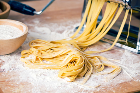 Photo pour fresh pasta and pasta machine on kitchen table - image libre de droit