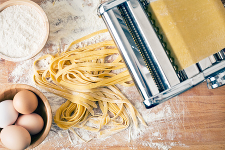 Foto de fresh pasta and pasta machine on kitchen table - Imagen libre de derechos