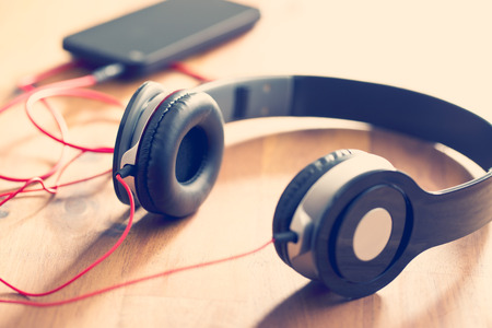 Photo for headphones with cellphone on wooden table - Royalty Free Image