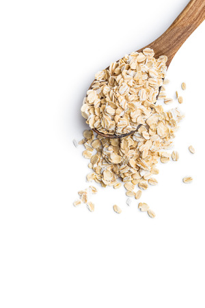 Foto de Dry rolled oatmeal in wooden spoon. Isolated on white. - Imagen libre de derechos