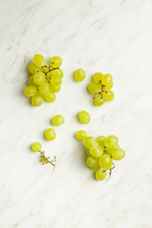 Foto de Tasty green grapes. White grape on white table. Top view. - Imagen libre de derechos