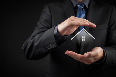 Photo pour Property insurance and security concept. Protecting gesture of man and symbol of house. - image libre de droit