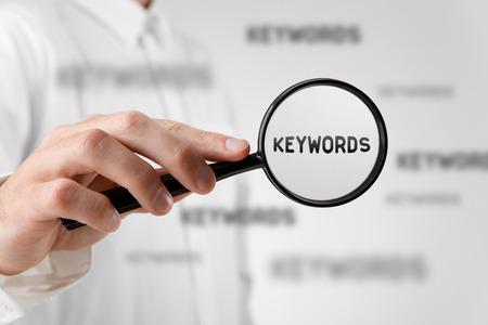 Foto de Find keywords concept. Marketing specialist looking for keywords (concept with magnifying glass). - Imagen libre de derechos