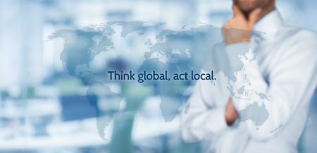 Photo pour Think global, act local. Globalization business rule. Businessman think about this rule. Wide banner composition, office in background. - image libre de droit