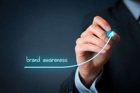 Foto de Brand awareness improvement concept. Brand manager draw growing graph with text brand awareness. - Imagen libre de derechos