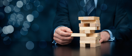 Photo pour Metaphor of risk in business. Risk management concept. Businessman remove one piece from tower. - image libre de droit