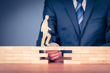 Foto de Customer care and support (help) and life insurance concept. Businessman representing company helps (support) customer (client) to overcome an obstacle. Problem solving with smart and simple solutions. - Imagen libre de derechos