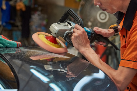 Photo for Hands Polishing Car With Rotary Car Polisher. Polishing On Car Paint Surface. Foam Pad In Blur Motion From Vibration Of Polisher Machine. Selected Focus - Royalty Free Image