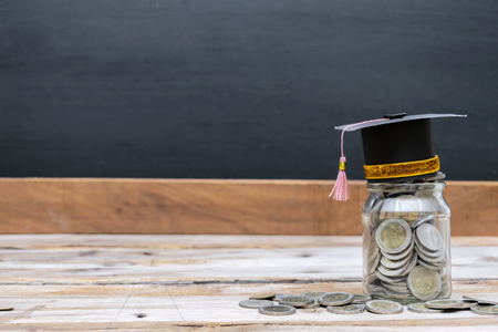 Photo pour Educational success concept. A glass jar with a lot of coins put in there until overflowing, Top with a degree cap. The background is a blackboard. Cost-effective investment with good returns. - image libre de droit