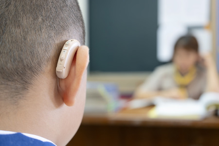 Photo for Students who wear hearing aids to increase hearing efficiency. Helps to be able to learn as much as a friend. The background is a teacher who is talking to him. - Royalty Free Image