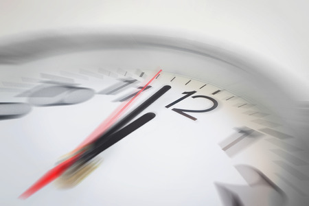 Foto de Close up of the hands of clock pointing nearly at 12 o'clock, business concept on deadline or rush hour. Using radial blur effect at 12 o'clock and rest is blurred. - Imagen libre de derechos