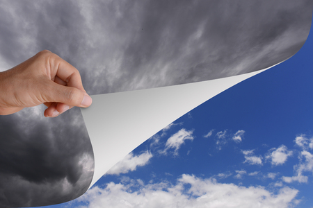 Photo pour Hand pick and pull paper or cutain from bad cloudy sky to be clear bright blue sky and white cloud. Conceptual illustration of optimistic idea, change, opportunity, or better step.  - image libre de droit