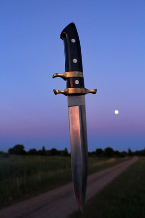 Photo for Combat knife of large size, against the background of the evening, the moon sky, in the pre-dawn fog, with artificial lighting. - Royalty Free Image