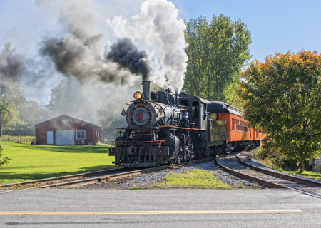 Foto per Old Vintage Steam Engine Arriving At The Train Depot - Immagine Royalty Free