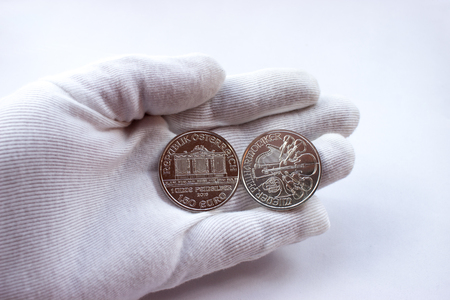 Photo pour On a white glove are silver coins of an investment silver from an Austrian mint. Vienna Philharmonic Orchestra. - image libre de droit