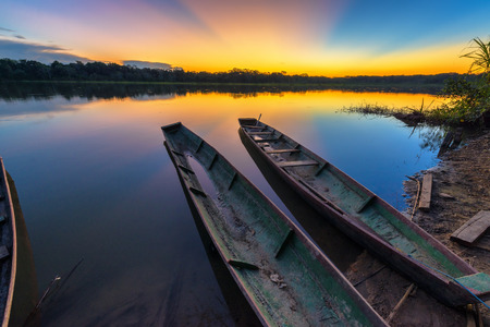 Photo for Dramatic sunset in the Amazon rain forest in Bolivia in Madidi National Park with two canoes in the foreground - Royalty Free Image