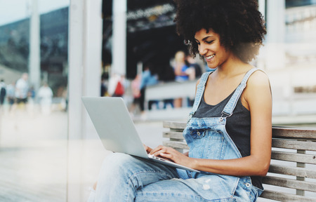 Photo for a smiley dark-skinned entrepreneur controls the work of her company remotely sitting on a wooden bench outside. - Royalty Free Image
