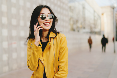 Foto de Smiling asian woman with long dark hair in sunglasses talking by a smartphone while walking the city street. Young entrepreneur making business calls by a mobile phone while going to coworking space. - Imagen libre de derechos