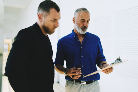 Photo for Two business parners wearing smart casual clothes discussing new sales report while standing in the bright office corridor. IT manager giving comments to the employee on a new project report. - Royalty Free Image