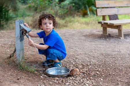 Foto de child opening a fountain for animals in park located in the middle of nature, - Imagen libre de derechos