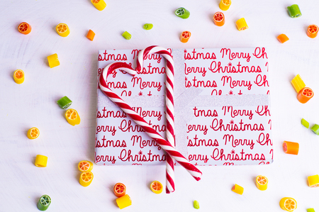Photo for Christmas gift wrapped in paper, caramel heart and candies - Royalty Free Image
