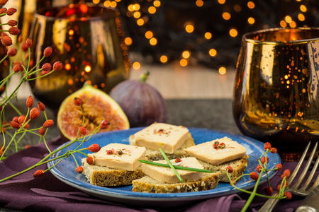 Photo for Foie gras on wholewheat bread with juicy ripe figs served as snacks at a festive celebration with colorful party lights in the background - Royalty Free Image