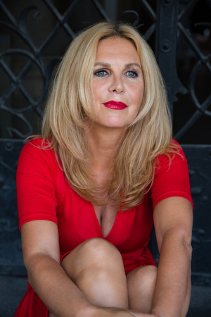 Photo for Portrait of long-haired blonde mature woman wearing red dress while sitting outdoors - Royalty Free Image