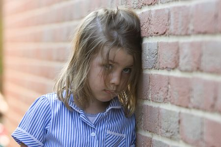 Shot of a Sad Young Blonde Girl against Brick Wall