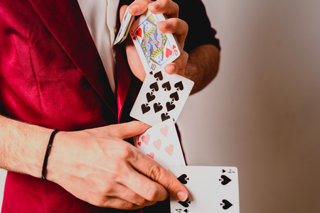 Foto de Young magician juggling a deck of playing cards. - Imagen libre de derechos
