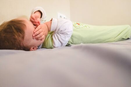 Foto de Baby sleeps on a bed in a poor marginal family. - Imagen libre de derechos