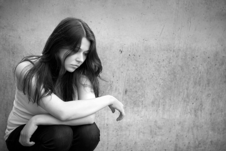 Foto de Outdoor portrait of a sad teenage girl looking thoughtful about troubles, monochrome photo - Imagen libre de derechos