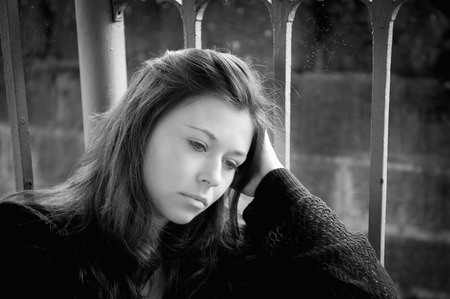 Outdoor portrait of a sad young woman looking thoughtful about troubles, monochrome