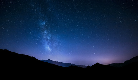 night sky panorama with moving stars and Milky way behind mountain