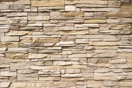Background of a contemporary stacked stone wall in warm brown tones