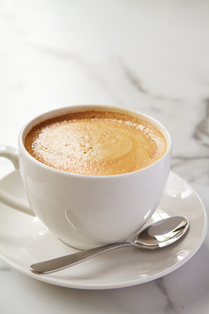 Photo pour Cappucino or latte milk coffee in white cup and saucer on a marble table - image libre de droit