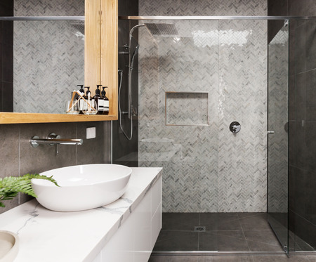Photo for Marble mosaic herringbone tiled shower feature wall in a contemporary ensuite bathroom - Royalty Free Image