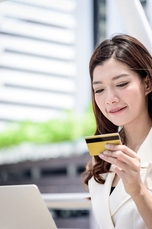 Foto für The asian business woman has shopping and buying with credit card from outside office with building and city background. - Lizenzfreies Bild