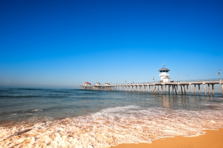 Foto de Huntington Beach Pier during early morning shows the tides changing with rushing surf moving up the shoreline. - Imagen libre de derechos